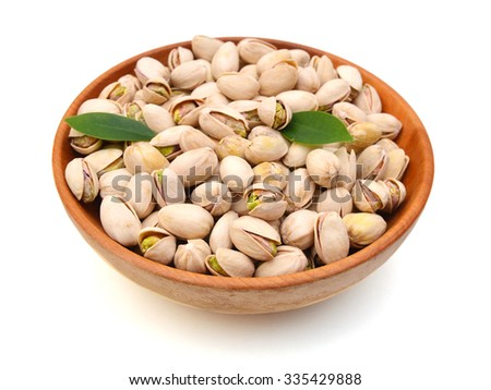 Heap of pistachios nuts isolated in wooden bowl om the white background  - stock photo
