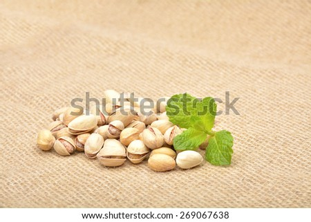 Heap of pistachios on old canvas  - stock photo