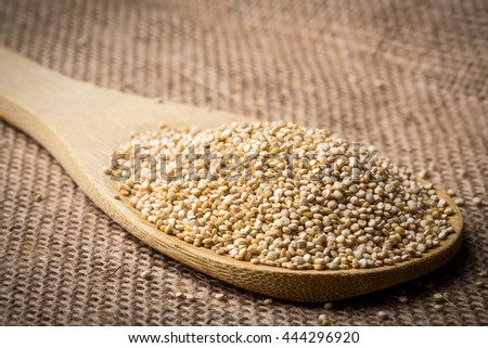 Heap of quinoa on wooden spoon and linen background, closeup.