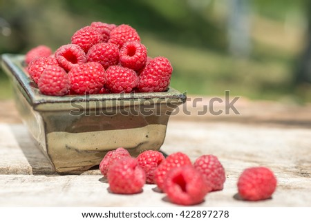 Heap of raspberries and a bowl with raspberries on wood boards - stock photo