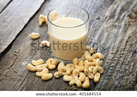 Heap of raw cashews and a glass of cashew milk, on wooden surface