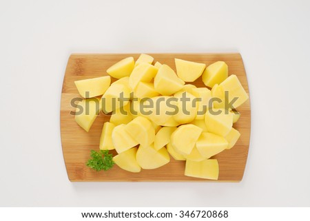 heap of raw diced potatoes on wooden cutting board - stock photo