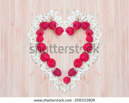 Heap of raw oatmeal flakes with raspberries in a shape of heart on a wooden cutting board, fresh morning breakfast, diet lifestyle - stock photo