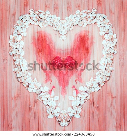 Heap of raw oatmeal flakes with raspberries in a shape of heart on a wooden cutting board, fresh morning breakfast. Drama, tragedy, love, sadness concept - stock photo