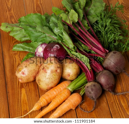 Heap of Raw Organic Potato, Carrot, Red Onion and Beet close up on wooden background - stock photo