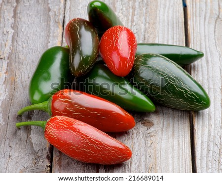 Heap of Red and Green Habanero and Jalapeno Chili Peppers isolated on Rustic Wooden background - stock photo