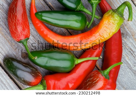 Heap of Red and Green Habanero and Jalapeno Chili Peppers isolated on Rustic Wooden background. Top View - stock photo