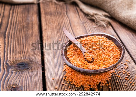 Heap of Red Lentils (close-up shot) on rustic background - stock photo