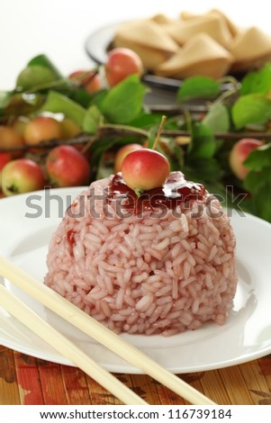 Heap of rice topped with sweet cherry sauce - stock photo