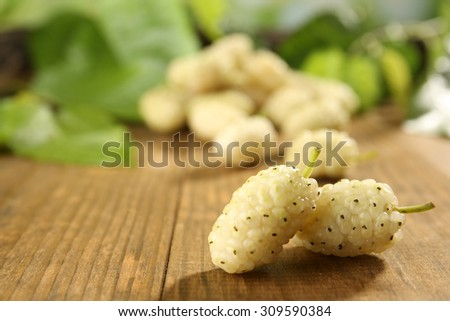 Heap of ripe mulberries with green leaves on table close up - stock photo