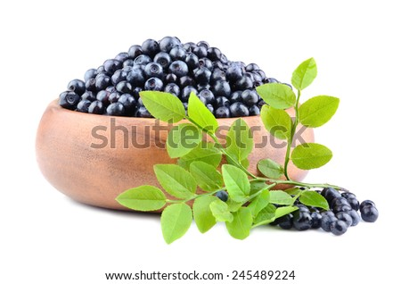 Heap of ripe  whortleberries with green leaves in a bamboo plate on a white background - stock photo