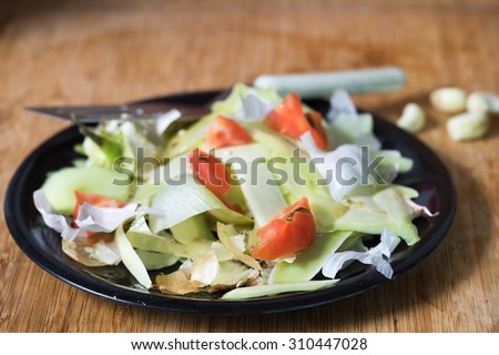 heap of rotten food waste closeup on a black plate - stock photo