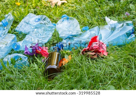 Heap of rubbish on grass in sunny park, plastic and glass bottles, bottle caps and paper, concept of environmental protection, littering of environment - stock photo