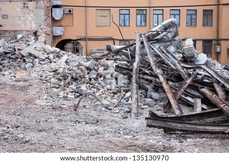 heap of rubble and a demolished building in the background - stock photo