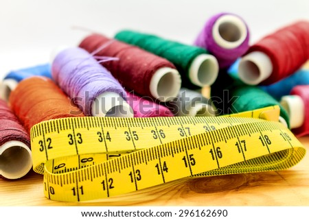 heap of sewing color bobbins threads and measure tape on wooden table with blur background   - stock photo