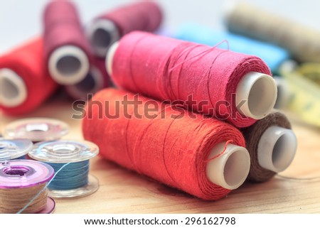 heap of sewing color bobbins threads on wooden table with blur background   - stock photo