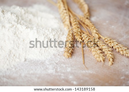 Heap of sieved flour and fresh eras of golden wheat lying on a bakery table depicting ingredients used in baking loaves of bread and pastries - stock photo