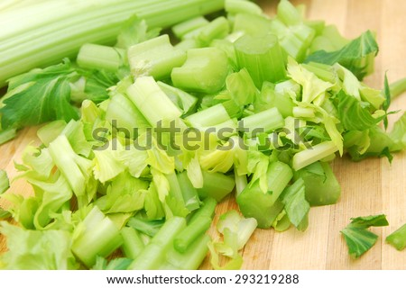 heap of sliced celery, isolated on wooden board - stock photo