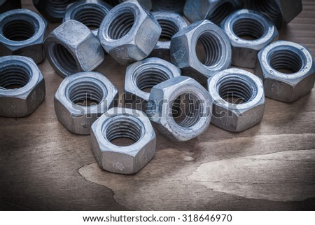Heap of steel threaded construction nuts on vintage wooden surface.