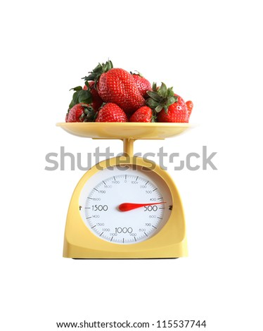 Heap of strawberry fruits lying on nice yellow kitchen scale. Isolated on white with clipping path - stock photo