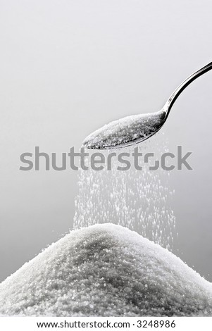 heap of sugar and a spoon - stock photo