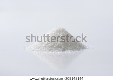 Heap of sugar in a porcelain bowl - stock photo