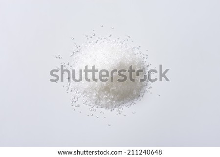 Heap of sugar on white background - stock photo