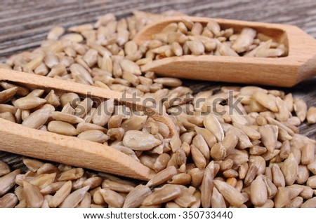 Heap of sunflower seeds with wooden spoon on wooden background, concept for eating and nutrition