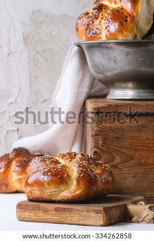 Heap of sweet round sabbath challah bread with white and black sesame seeds in vintage metal bowl on wooden chest and on small cutting board over white table with plastered wall at background. - stock photo