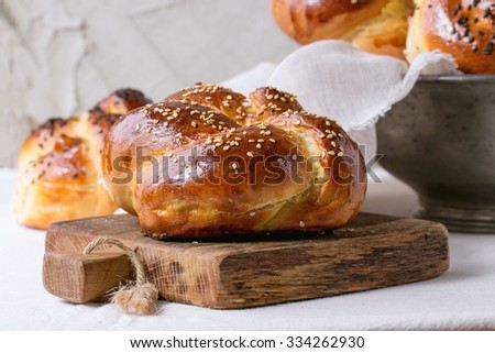 Heap of sweet round sabbath challah bread with white and black sesame seeds on small cutting board over white table with plastered wall at background. - stock photo