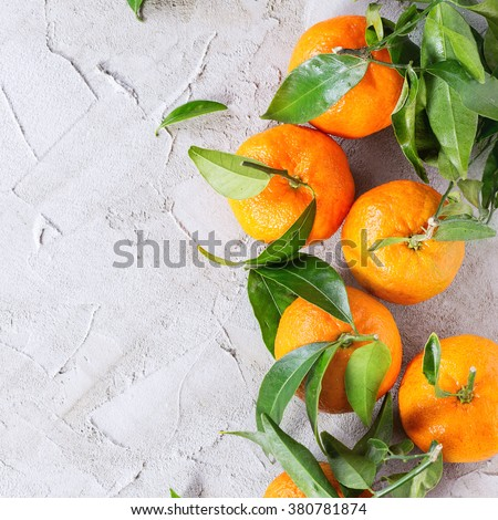 Heap of Tangerines with leaves over gray plaster surface. Top view. Square image  - stock photo