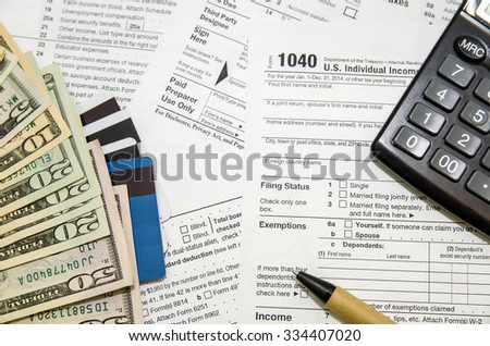 Heap of tax form, credit cards, the calculator, a ball pen and money