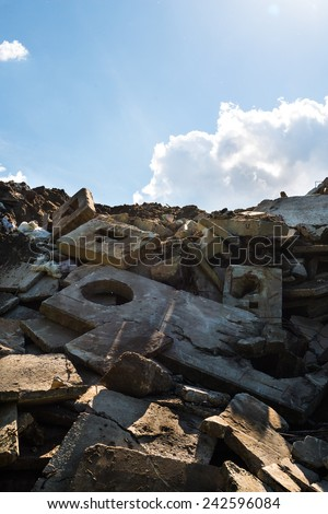 Heap of the damaged concrete blocks. Construction debris. Blue sky background, - stock photo
