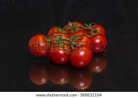 Heap of the fresh tomatoes on a mirror black wooden table - stock photo