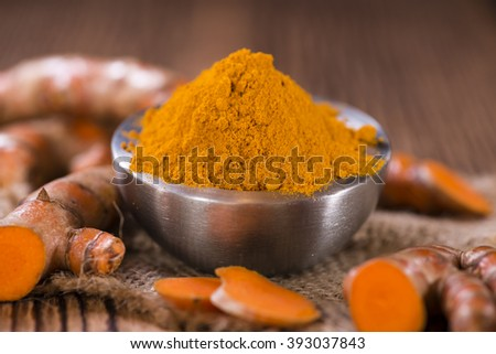 Heap of Turmeric (selective focus) on an old wooden table