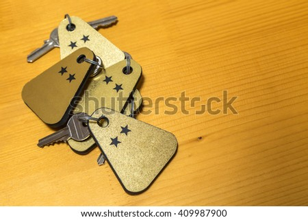 Heap of two stars hotel room keys on a wooden table.