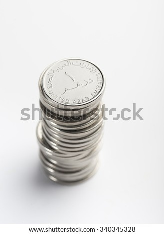Heap of UAE one dirham coins. Over the shoulder view. - stock photo