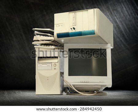 Heap of used computers and monitors on steel background - stock photo