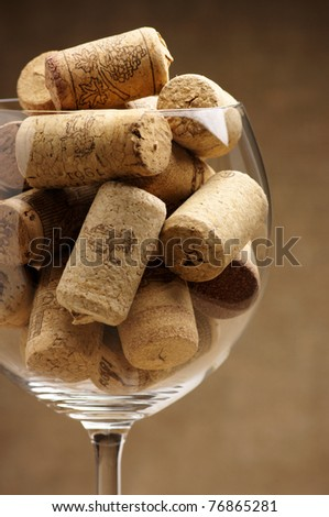 Heap of used vintage wine corks in wineglass close-up. - stock photo