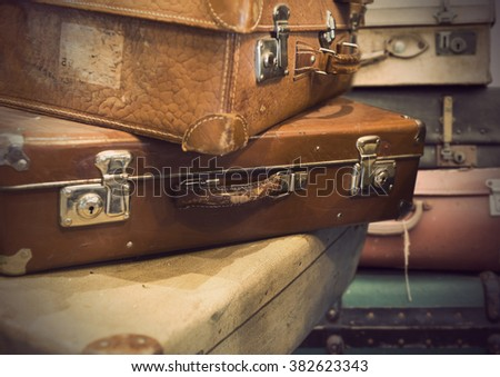 heap of vintage suitcases in sepia tone