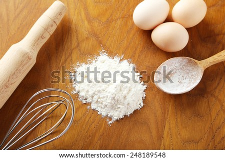 Heap of wheat flour with eggs, rolling pin and whisk on brown wooden background - stock photo