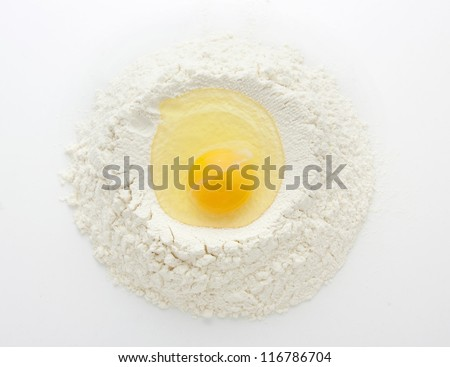 heap of wheat flour with raw egg over white