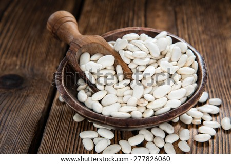 Heap of White Beans (close-up shot) on an old wooden table) - stock photo