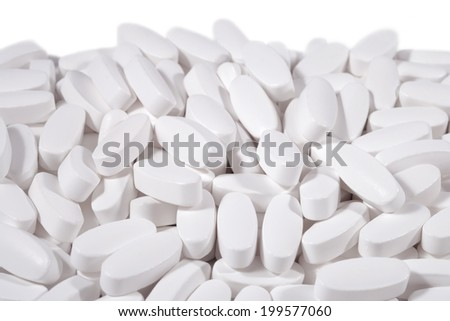 Heap of white pills on a white  background - stock photo
