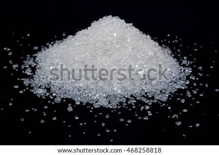 Heap of white sugar on a black background, close-up.
