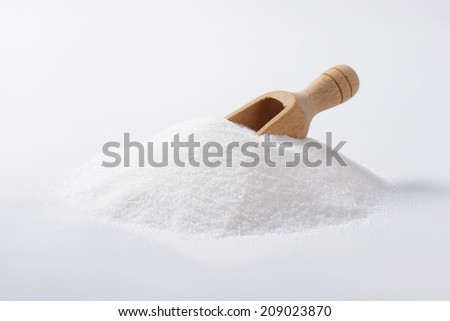 Heap of white sugar with a wooden spoon - stock photo