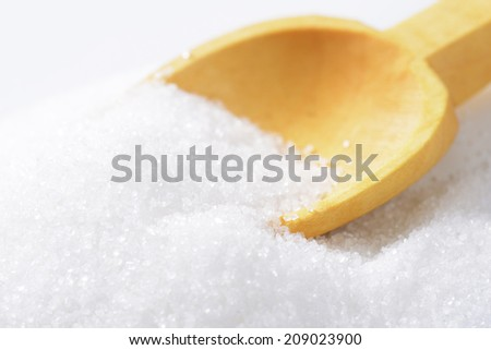 Heap of white sugar with a wooden spoon
