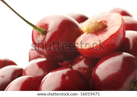 Heap of whole and cut cherries on white background. - stock photo