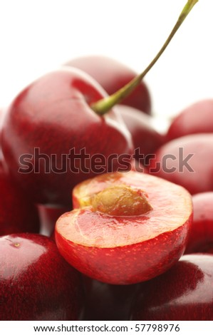 Heap of whole and cut cherries on white background.