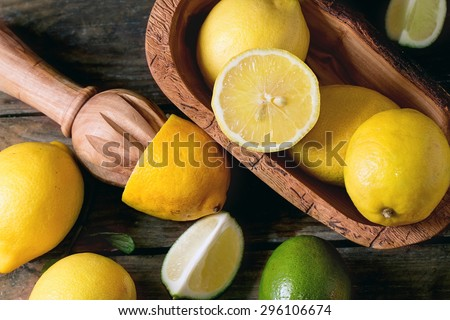 Heap of whole and sliced lemons and limes in olive wood bowl and citrus reamer over wooden background. Top view - stock photo